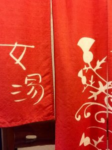 "At the entrance for ladies' bath, there is a hanging ""Noren"". A character of ""Onna-yu"" (hot spring for women) is written in it."