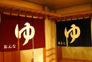 "In ""Onsen"" (hot springs) or ""Sentou"" (public baths), there is a hanged ""Yu-Noren"". A character of ""Yu"" is written in it."